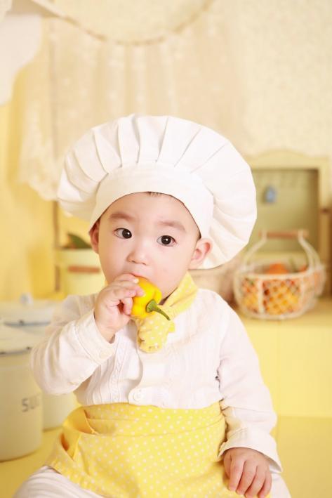Foto af en baby, der er klædt ud som kok