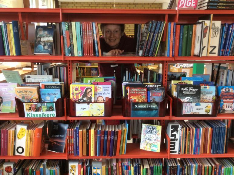 Foto af Dorte, der kigger ud gennem en bogreol